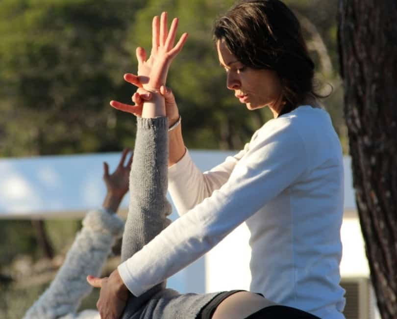 Opale-adjusting-in-Trikonasana-at-Yoga-retreat-Ibiza