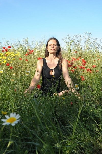Opale in Meditation in a field of flowers in Ibiza