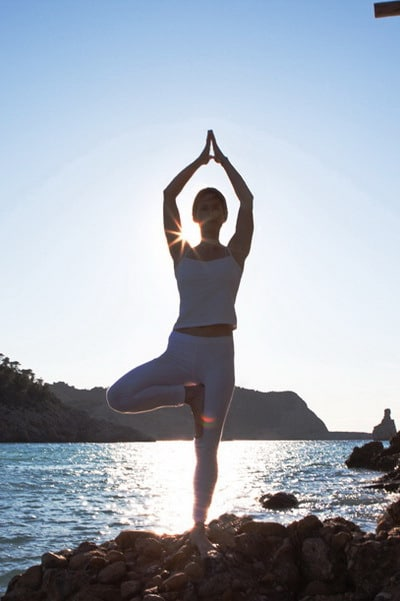 Opale in Vikrasana tree pose at beniras beach Hatha Yoga Ibiza