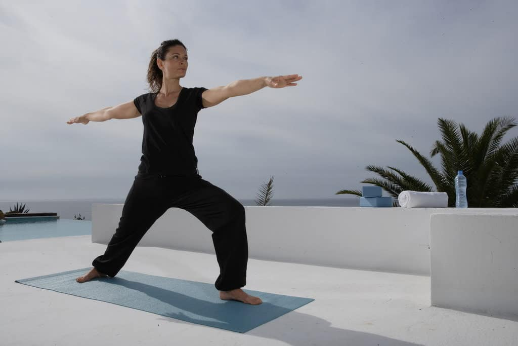 Opale in Virabhadrasana Warrior pose for Decathlon photo shoot in Ibiza
