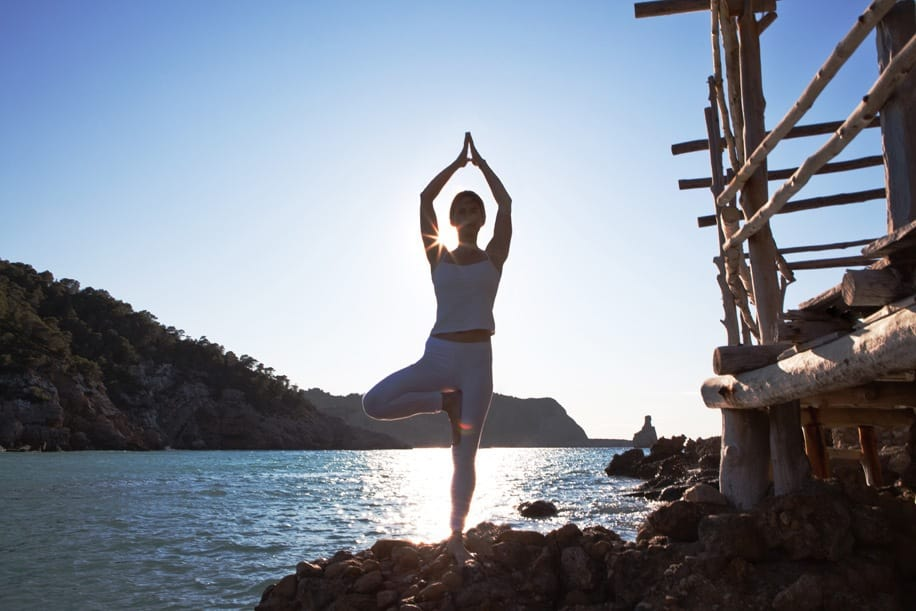 Opale in Vrkasana Tree pose Yoga at Beniras beach in Ibiza