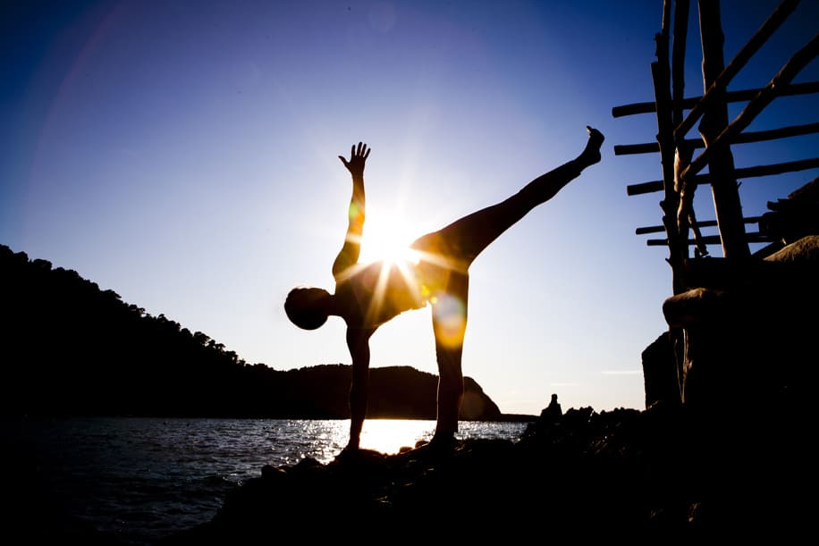 Opale in ardha candrasana half moon pose at sunset in Beniras Yoga retreat Ibiza