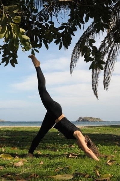 Opale in eka pada adho mukha svanasana cala Martina beach Vinyasa Yoga Ibiza