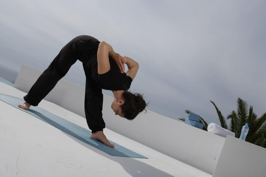 Opale in parsvottanasana side stretched out pose for Decathlon photo shoot in Ibiza