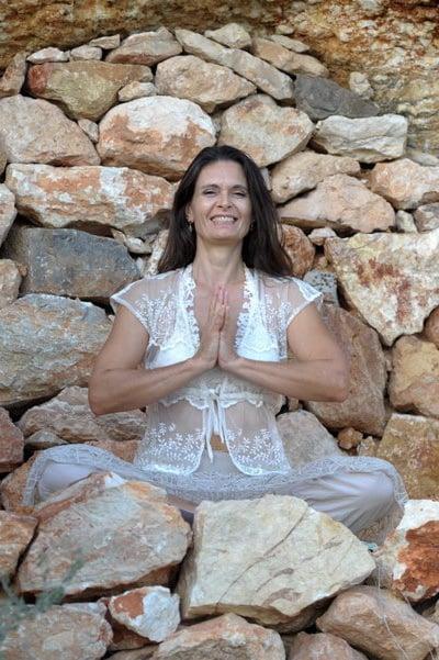 Opale in sukhasana meditation pose hands in anjali mudra in a cave Ibiza 1