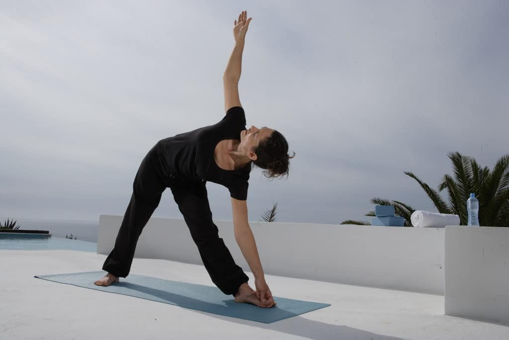 Opale in trikonasana triangle pose for Decathlon photo shoot in Ibiza