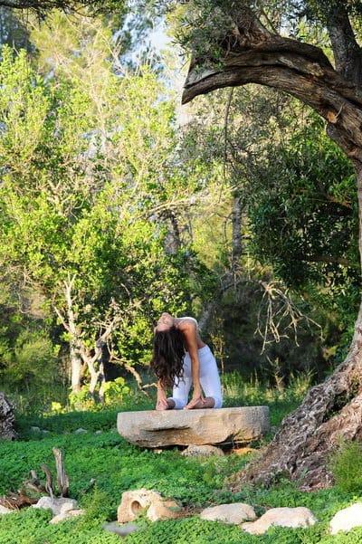 Opale in ustrasana Yogilates by the loive trees in Ibiza