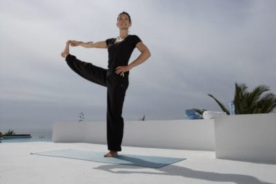 Opale in utthita hasta padangusthasana extended hand to big toe posefor Decathlon photo shoot in Ibiza
