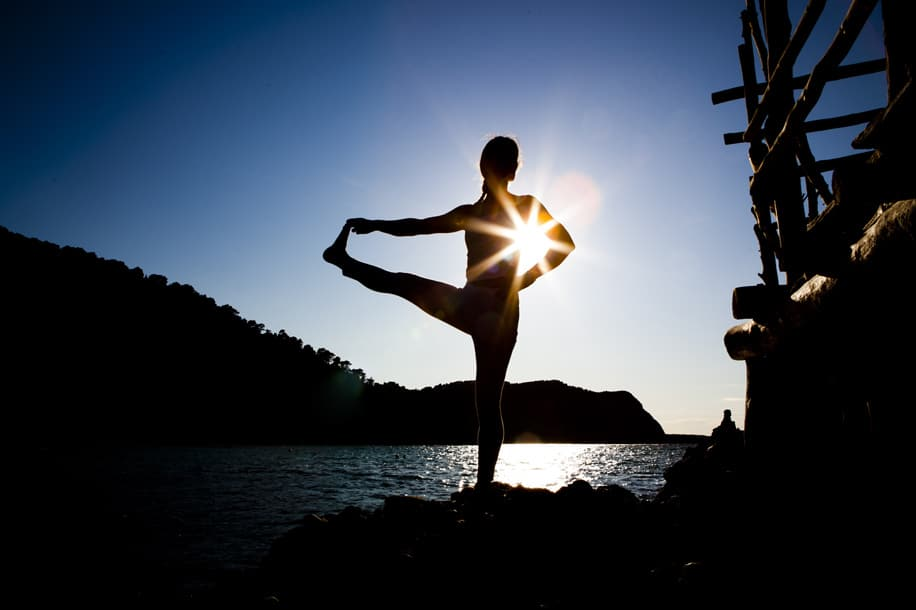 Opale in utthita hasta padangusthasana for sunset at Beniras beach Ibiza