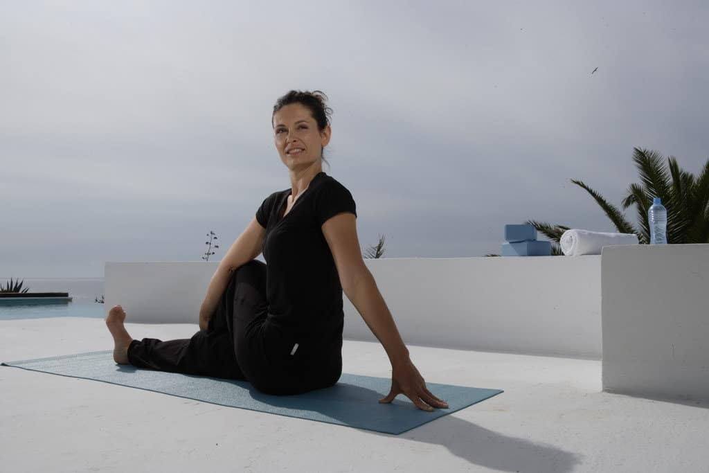 Opale in variation for ardha matsyendrasana 1 sitting stwist pose for Decathlon photo shoot in Ibiza