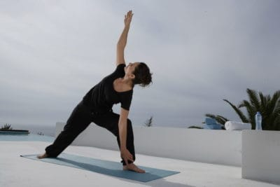 Opale in variation for parsvakonasana side angle pose for Decathlon photo shoot in Ibiza