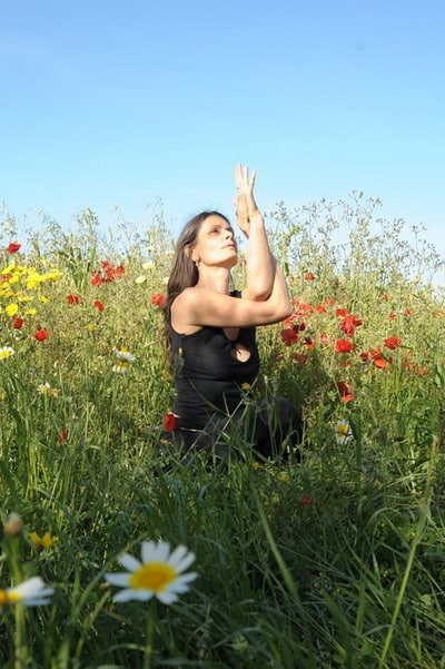 Opale in variation of Gomukhasana Hatha Yoga in a field of flowers biza
