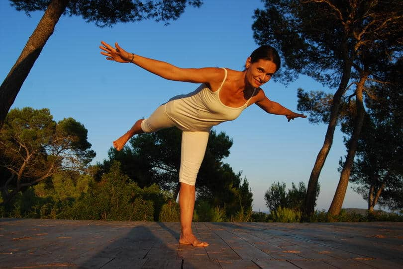 Opale in variation of Virabhadrasana 3 warrior pose at Yoga retreat Ibiza