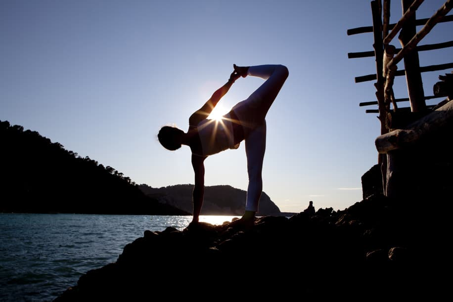 Opale in variation of ardha candrasana half moon pose at sunset in Beniras Yoga retreat Ibiza