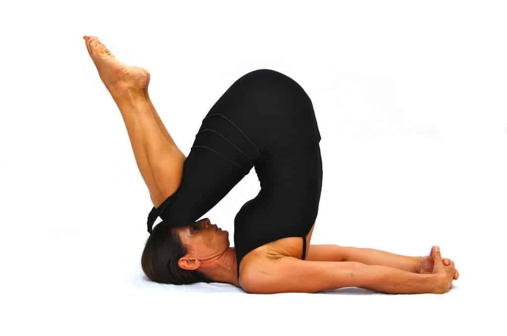Halasana plow pose variation Opale Yoga Ibiza