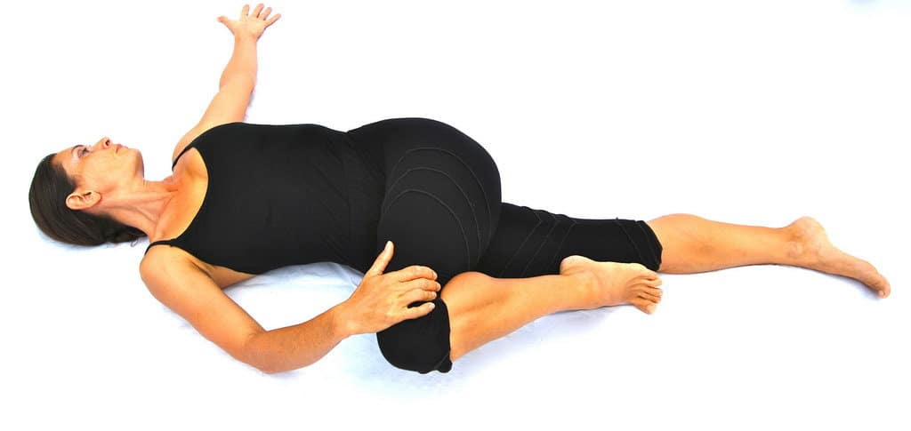 Parivrtta supta padangusthasana reverse reclined big toe pose with knee bent Opale Yoga Ibiza