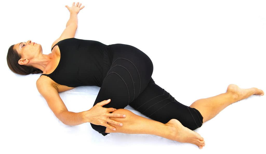 Parivrtta supta padangusthasana variation reverse reclined big toe pose variation with 2 knees bent Opale Yoga Ibiza