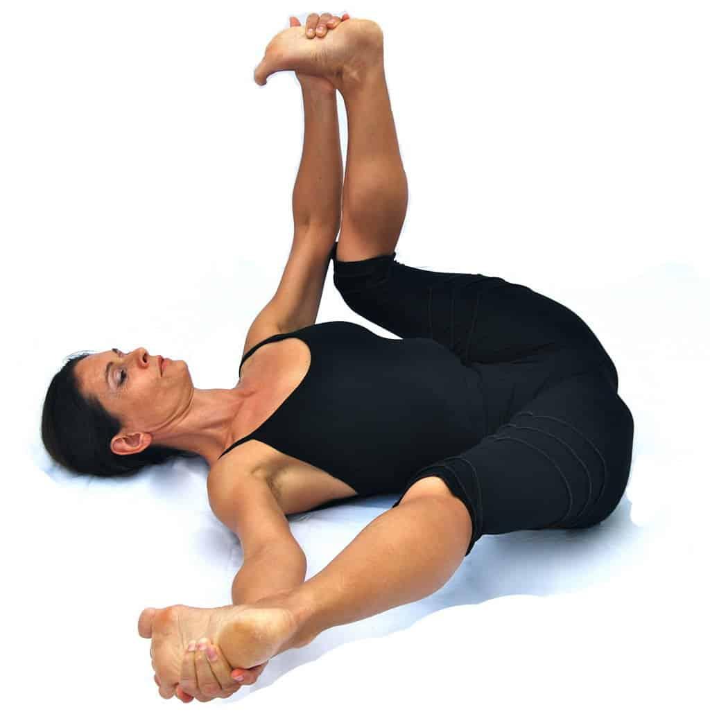 Sukhabalasana variation happy baby pose with 1 leg extended sideways Opale Yoga Ibiza